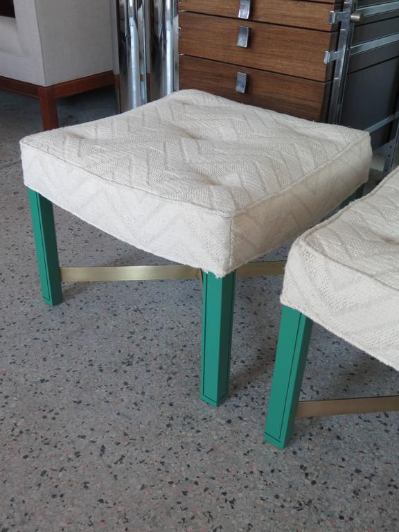 A pair of Paul Laszlo ottomans. Green laquered notched legs with brass cross stretchers.