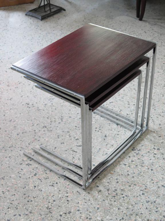 An unusual set of three nesting tables, rosewood or chrome cantilevered legs.