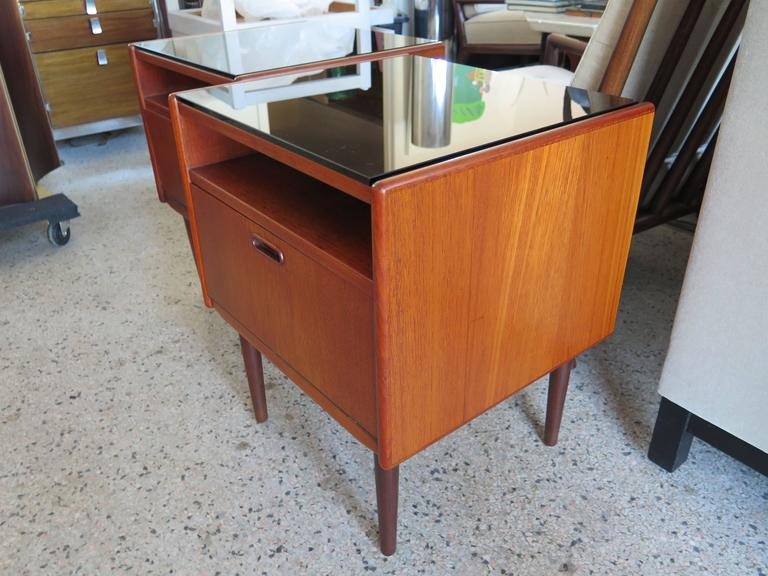 A pair of Classic night stands by Borge Mogensen for Soborg Mobler, Denmark, circa 1960s. Teak with white laminate drop fronts and glass tops. Open shelf above drop front for extra storage.