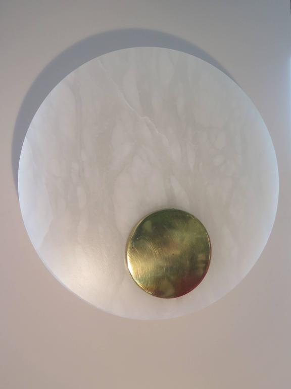 A set of three unusual alabaster and polished brass sconces by Lightolier (signed). Simple geometric design-circle in a circle, glass diffuser.