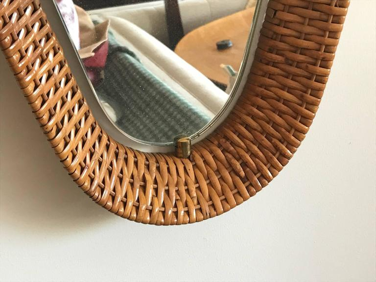 An unusual Italian mirror, circa 1950s. Beautiful caning with brass details. Shaped like a diamond with rounded corners and a real Mid-Century Modern look.