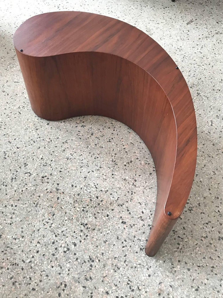 An unusual coffee table in the style of Vladimir Kagan, shaped like a comma. Biomorphic glass, walnut base.