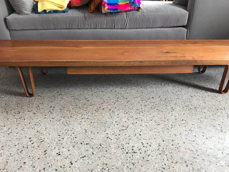 "A classic Edward Wormley for Dunbar ""Long John"" bench in sap walnut. Features a pull put drawer and hairpin legs. Measures 84"" L, 19"" D, 11.75"" H."