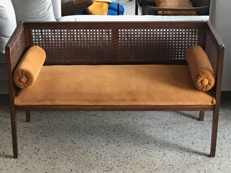 "An elegant baquette-entry bench. Caned sides and back, upholstered seat with bolster cushions. Seat height is approximately 16.5""."