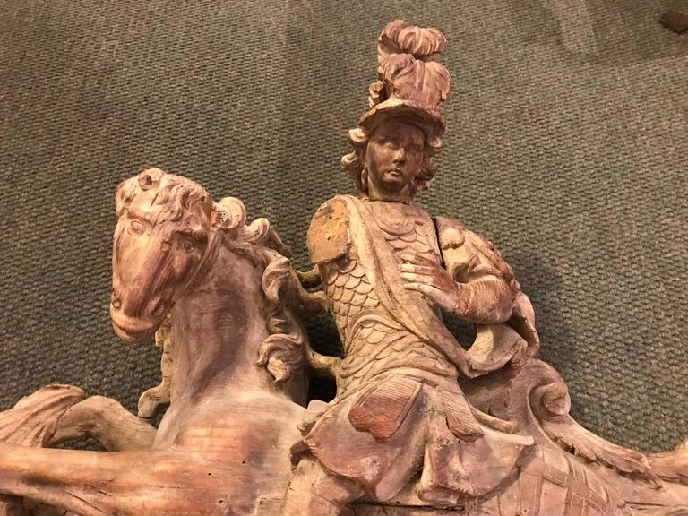 A very fine and dynamic depiction of Saint George slaying the dragon, carved from chestnut. French, 18th century. With scroll-work and cross hatching typical of Rococo carving. Most likely a 'boiserie' over-door or possibly from a choir screen.
