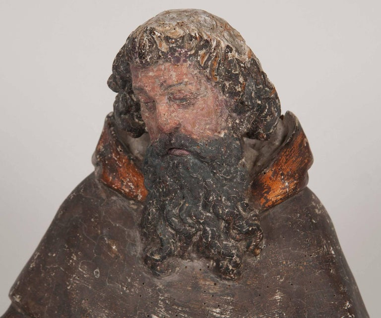 Italian carved and polychromed figure of a male saint. Shown holding an open book in his right hand with flames at his feet, mid-16th century. Though the surface is worn from age, it retains some of it's original surface. Nice scale at close to 3