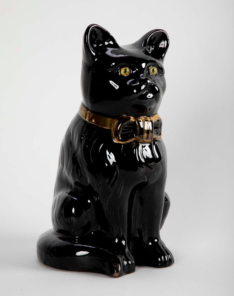 A charming seated glazed ceramic black cat with yellow glass eyes and gilt bow around neck. What I find most appealing about this fellow is the rather serious look on his face. French Art Nouveau period. Emile Galle is known for his colorful cats