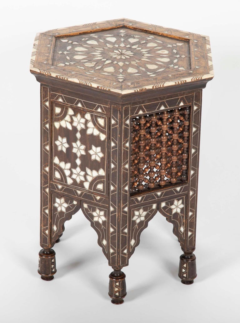 A Turkish hexagonal hardwood side table with bone, metal and mother-of-pearl inlay throughout. This handsome table has alternating side panels of inlay and the delicate wood turnings that make this type of furniture so distinctive.