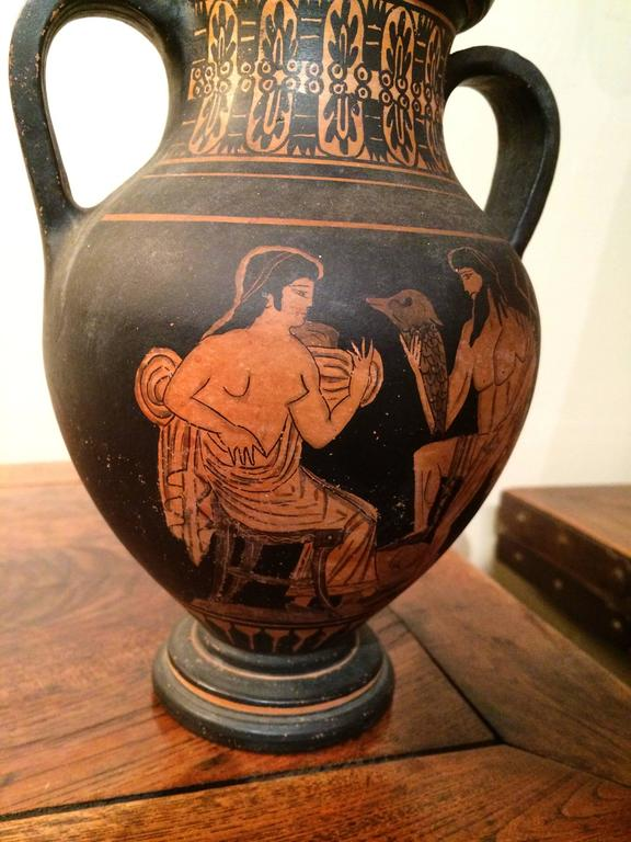Classical Greek two handled vase in the ancient style depicting a mythological scene with Neptune presenting a porpoise to a seated woman or goddess.