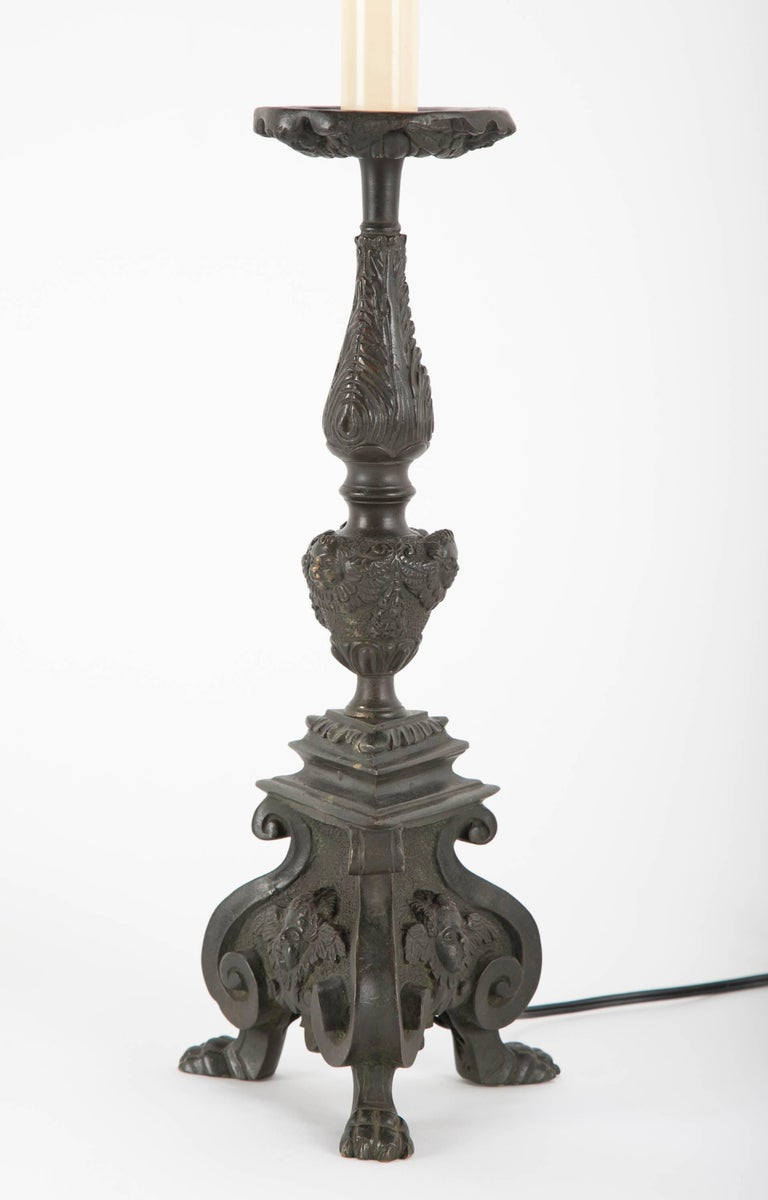 Pair of Italian Baroque style bronze candlesticks wired as table lamps. With tripod footed bases decorated with winged putto faces on each side. Additional putti on the center knob and the underside of the drip pan. Deep greenish back patina. With