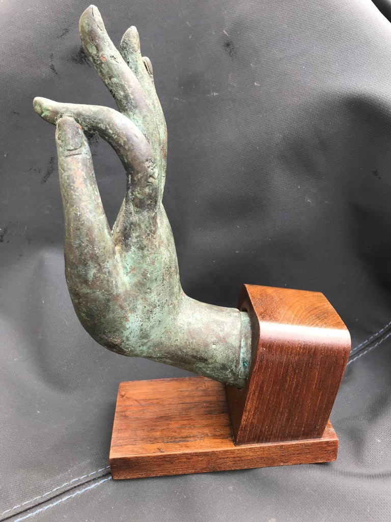 Beautifully realized bronze hand of Buddha, in the Vitarka mudra, mounted on a walnut base. Nice verdigris patina. 19th century, possibly earlier. Great gift for the yogi in your life.  The Vitarka mudra symbolizes teaching and discussion. It shows