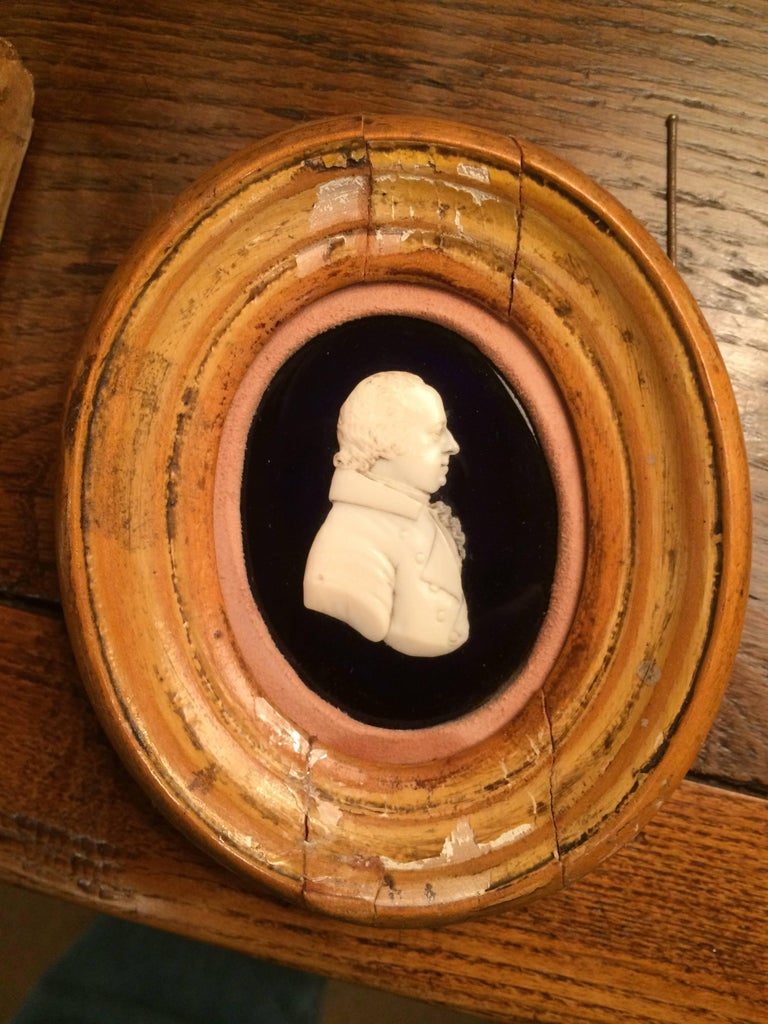 Very fine English early 19th century carved bone portrait of a nobleman or sea captain laid down on black glass and set in an oval walnut frame with an unusual suede mat. The gentleman shown in right profile wearing a collared coat with a ruffled