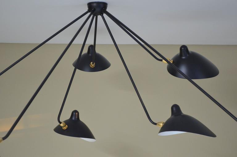 This ceiling lamp is an authorized re-edition, produced by the Serge Mouille family at the site of his original workshop.  With seven adjustable shade on fixed arms of different lengths, this lamp is a bold statement one that will command the