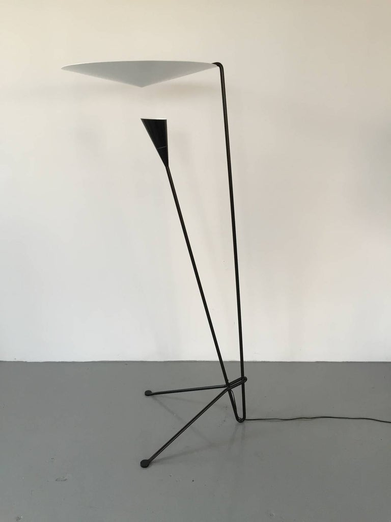 Dynamic lines and an innovative means by which the light is dispersed are signatures of this Michel Buffet lamp. Light shines on the conical disc above from the shade below and is reflected out.
