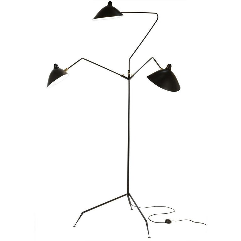 This is the most versatile lamp of the Mouille collection. Each 'chapeau' shade can be oriented differently. Sculptural in form with three rotating arms, it stands majestically on a tripod base ending with tapered legs. Accent pieces are in brass.