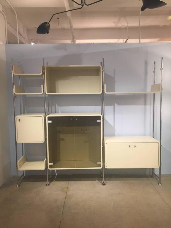 This stylish shelving unit utilizes a simple yet clever adjustable system for hanging the various shelves and cabinets that is highly adjustable, visually appealing, and also very stabile.