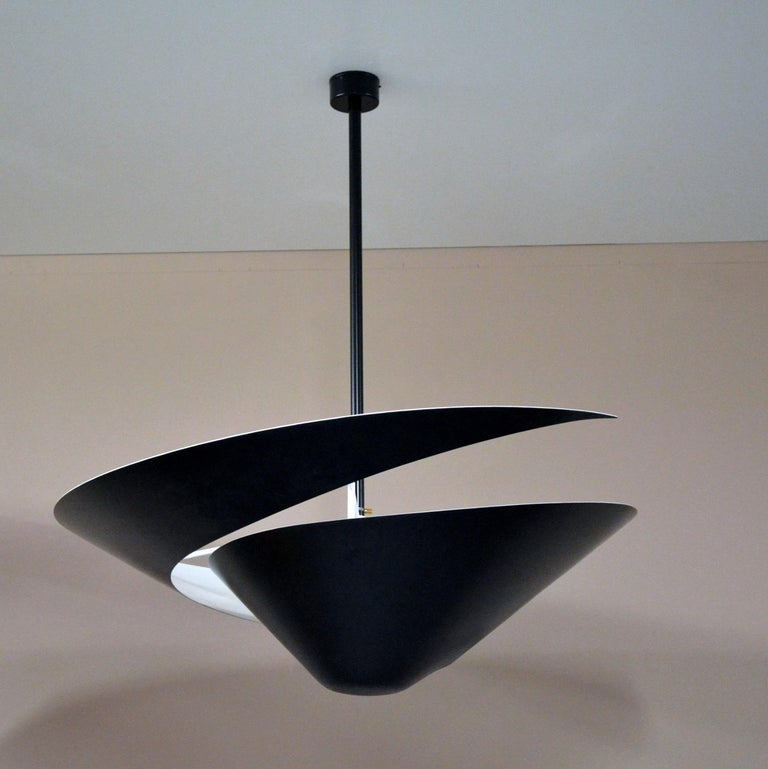 A snail shell provides the inspiration for this lamp with its swirling cut-out in the circular shade. Light projects downward through the opening while the shade causes light to reflect from the ceiling.  Available in black or white.