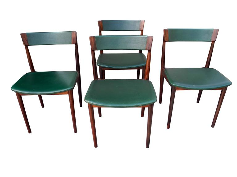 This set of Henry Rosengren Hansen chairs produced by Brande Møbelindustri have dark green leather upholstery and solid rosewood frames. Chairs are branded underneath. Matching rosewood dining table also available but sold separately. #39.
