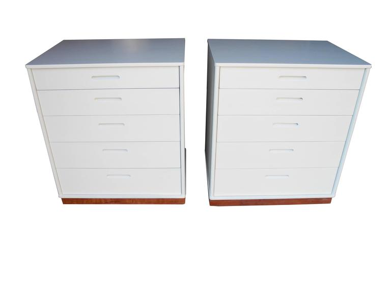 These small white matching dressers or nightstands equipped with five drawers each are painted in a linen white and lacquered. The plinth is wrapped in leather and the rounded side edges are examples of Wormely's attention to detail.