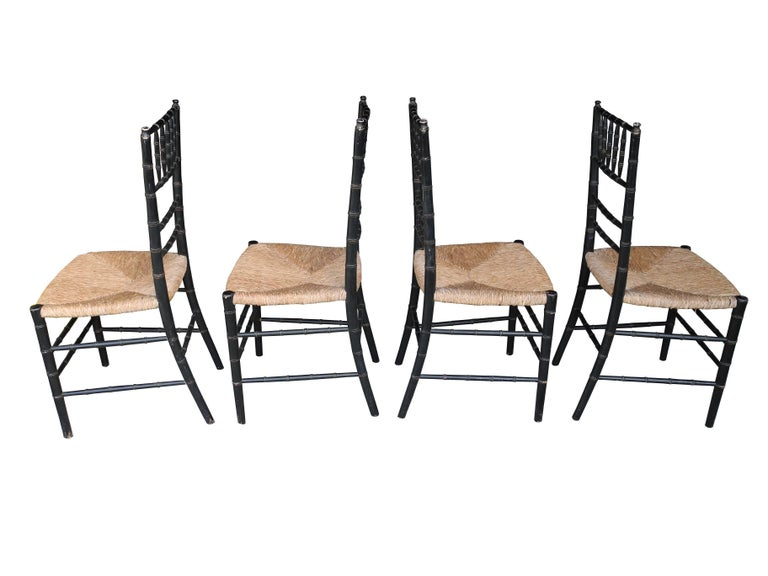 This set of four faux bamboo chairs are made of painted wood frames and rush seats. Slight patina and wear to the frames give them that extra vintage charm.