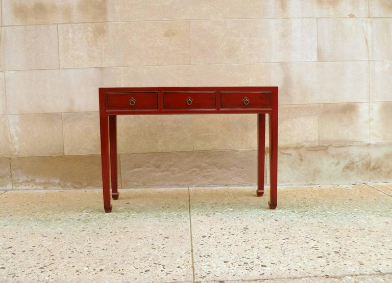 A simple and elegant red lacquer table with three-drawers, brass ring pulls.  We carry fine quality furniture with elegant finished and has been appeared many times in