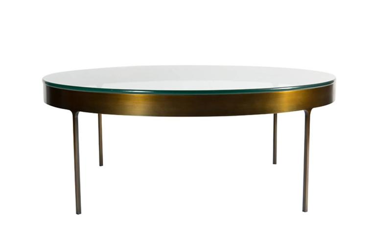 Bronze ring cocktail table with fitted clear glass top. Solid flat bar metal frame with on thin profile legs with interior radius joint detail.  Custom orders have a lead time of 10-12 weeks FOB NYC. Lead time contingent upon selection of
