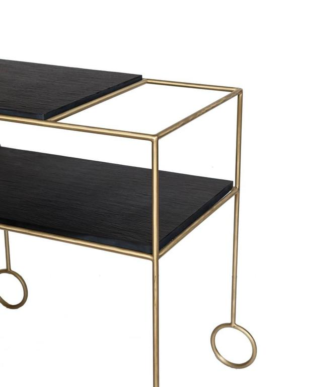 Biron satin brass frame bar cart with natural cleft finish slate tops. 