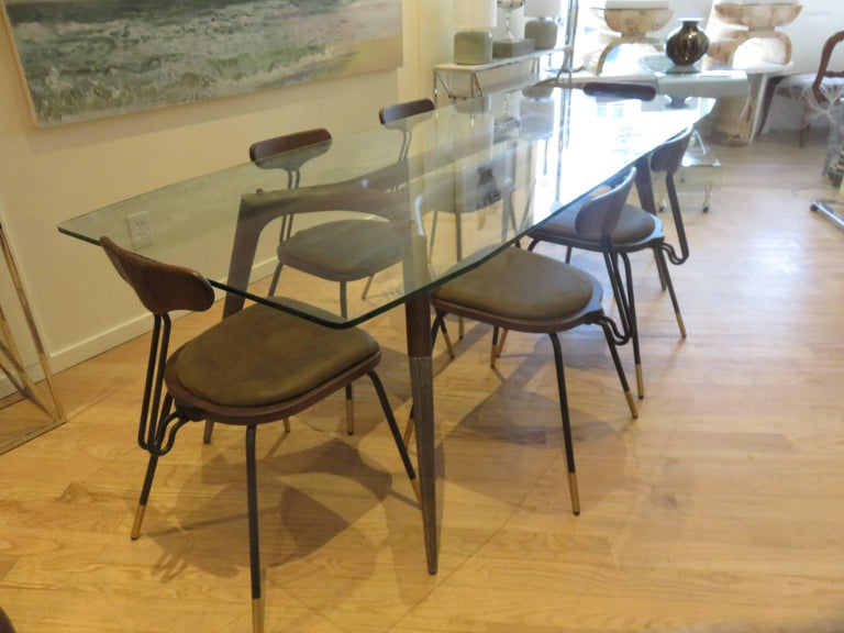 Walnut wood base with hammered steel to half of leg, half inch thick glass top,with cut angles on all four corners. Six matched chairs with rich brown leather seats,premium quality Italian construction. The table can be purchase separately as can