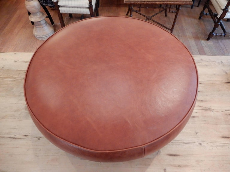 A Danish Mid Century Modern low ottoman or stool,measuring 30 inches round and 11 inches high,flat enough for a tray top. New premium leather in a rich  cognac brown,wood legs with bronzed metal feet.