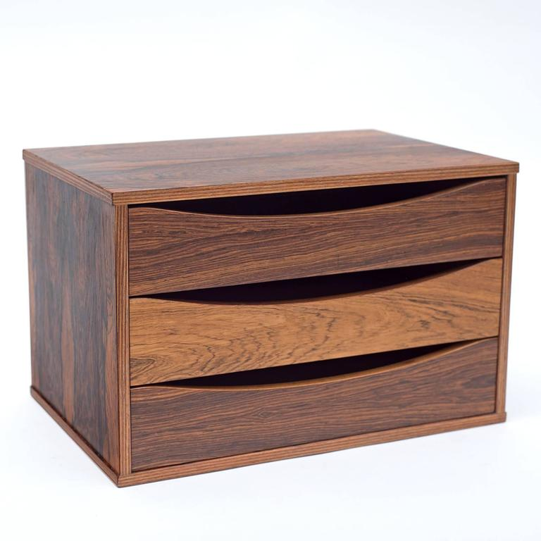 A practical and attractive small chest of drawers that could be used for a variety of purposes. Usually found in teak this is an outstanding rosewood version.