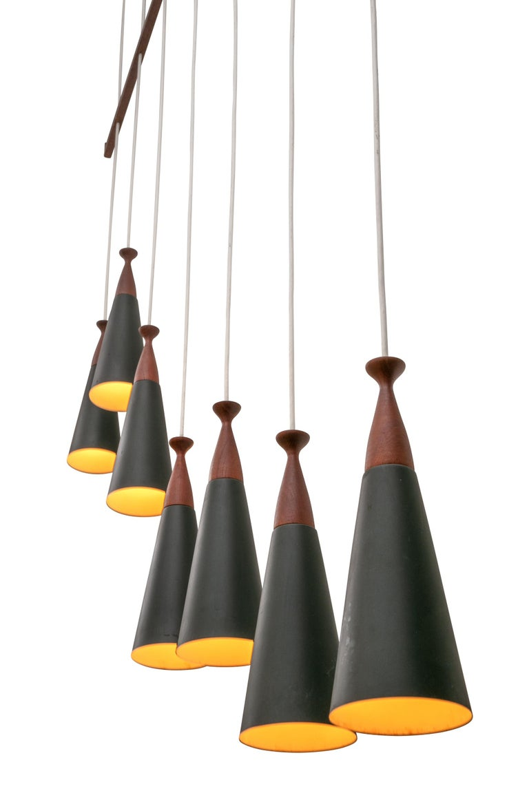 Impressive in it's scale and teak elements. The individual pendants could be adjusted in height if desired.