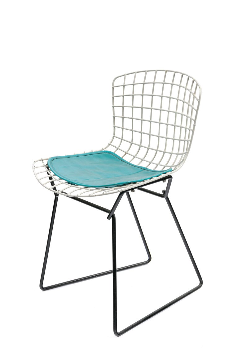 A universally recognized design, this Bertoia child's chair has a white seat with a black base and the original turquoise seat pad.