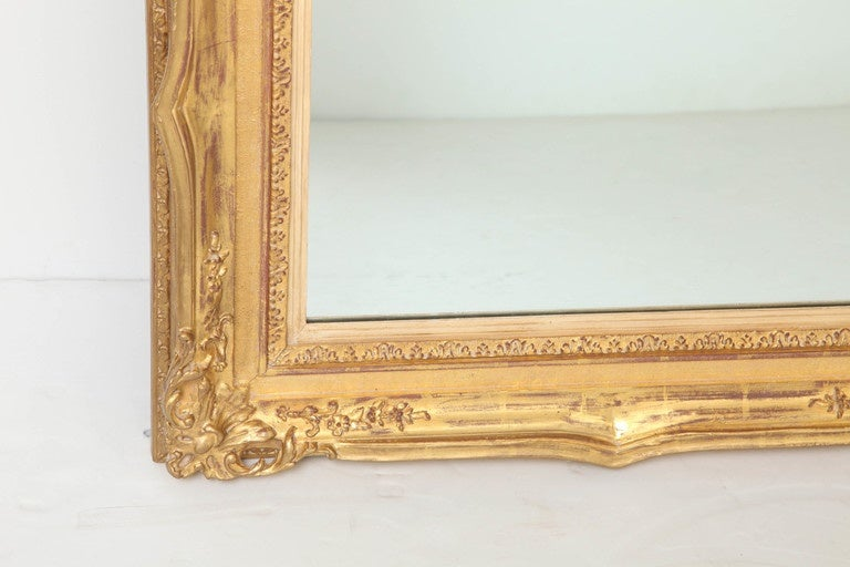 Large antique mirror from the turn of the century. Very beautifully carved wood frame with gold leaf.