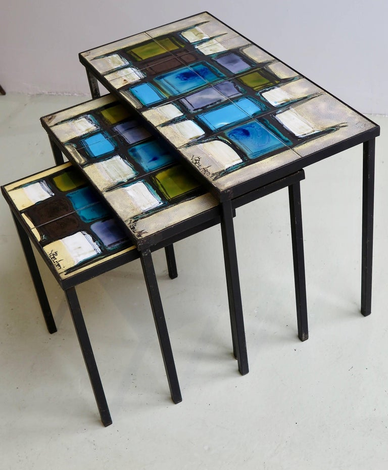 Nest of three tables with hand-painted ceramic tiles on black metal base frame by Belarti, Belgium, circa 1960. Signed.