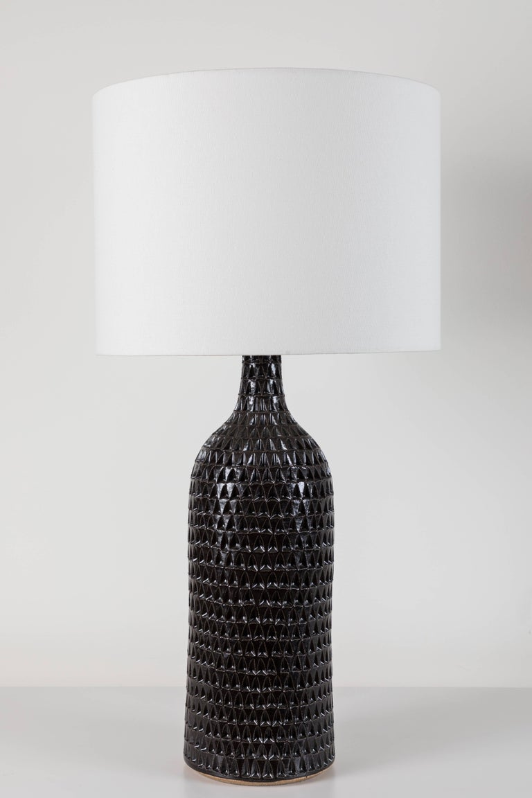 Pair of extra large black carved bottle lamps by Victoria Morris.