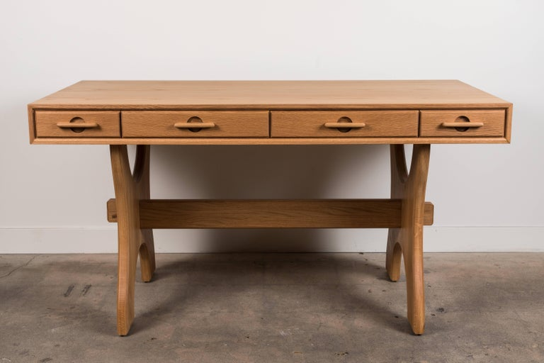 The Ojai Desk has four drawers and features solid American walnut or white oak trestle legs. The drawer handles are made of solid carved wood. Shown here in Natural Oak.  Available to order in various finishes with a 10-12 week lead time.