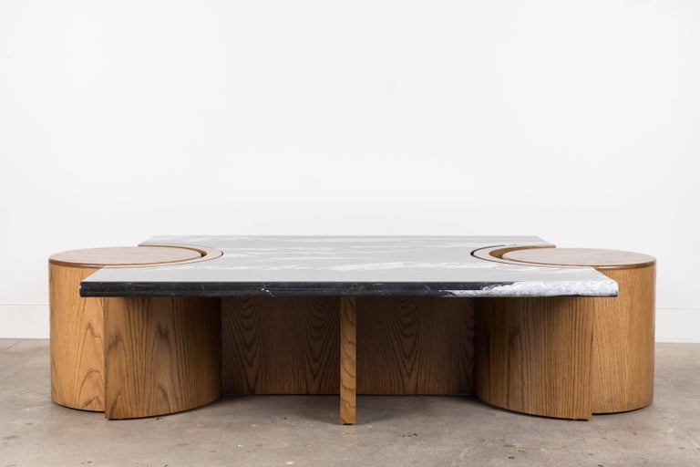 The Prospect Coffee Table features a stone top that rests atop a sculpted American walnut or white oak base with two cutouts for drum tables on either end. Shown here in Negra Marquina Marble and Oiled Oak.  Dimensions: 64