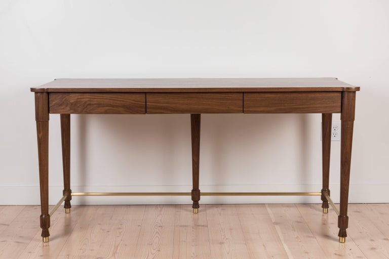 The Niguel Desk features brass cap feet, a brass cross-stretcher with lacquered interior drawers and an optional inset leather top. Shown here in Light Walnut.  Available to order in various finishes with a 10-12 week lead time.