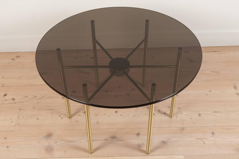 The Radial Side Table has a metal radial spoke base and a 1/2 inch glass top. Shown here in Satin Brass and Smoked Glass.  Available to order in various finishes with a 10-12 week lead time.