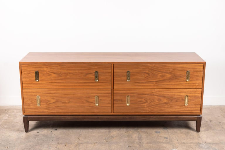 The 4-drawer Arcadia chest features four drawers, cast brass hardware, and a sculptural solid American walnut or white oak base. Shown here in light walnut with dark walnut base.  Available to order in various finishes with a 10-12 week lead