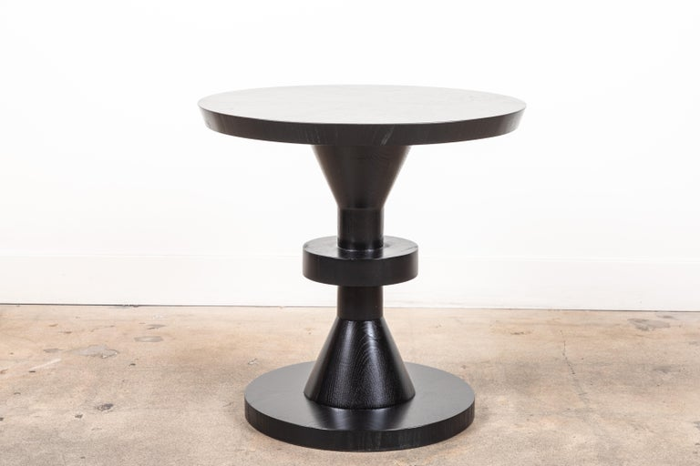 The Capitola table features a series of geometric shapes stacked on top of each other with solid wood details. Available in American walnut or white oak. Shown here in ebonized oak.  Available to order in customer's own material with a 10-12 week