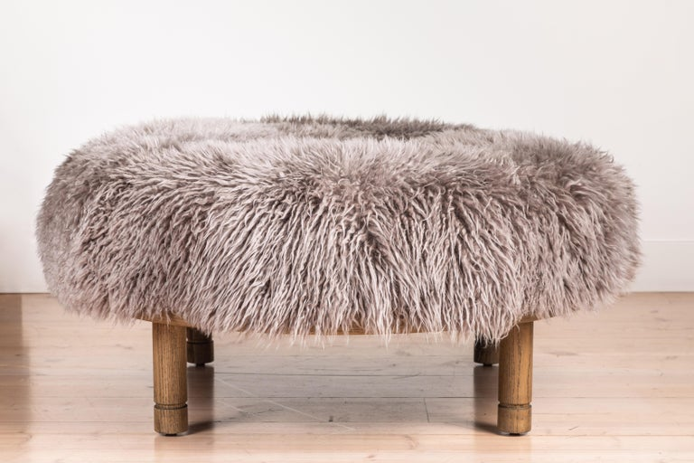 The Moreno Ottoman features a round solid wood base with four cylindrical legs and an upholstered top. Available in American walnut or white oak. Shown here in Smoked Oak and Garret Shearling. 