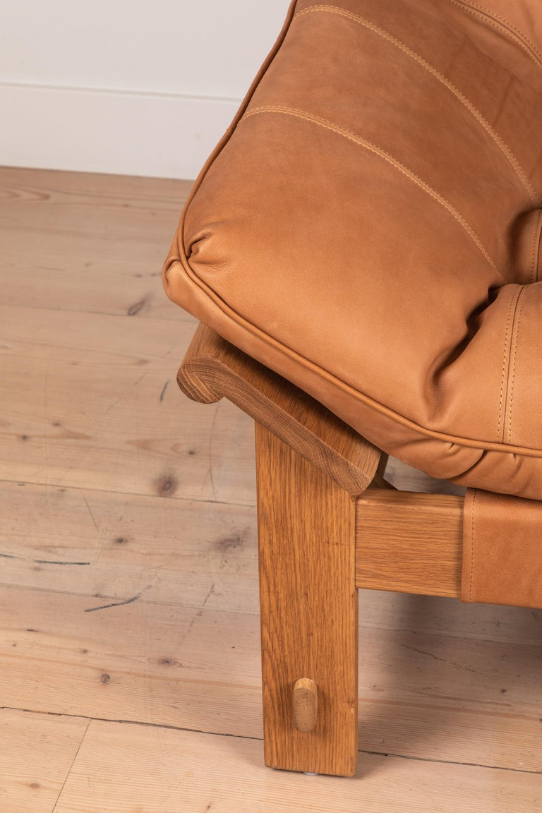 The Ojai lounge chair features a solid white oak or solid walnut base and a single tufted leather cushion with leather straps. Shown here in deer tan Leather and oiled oak.   Available to order in various finishes with a 14-16 week lead time.