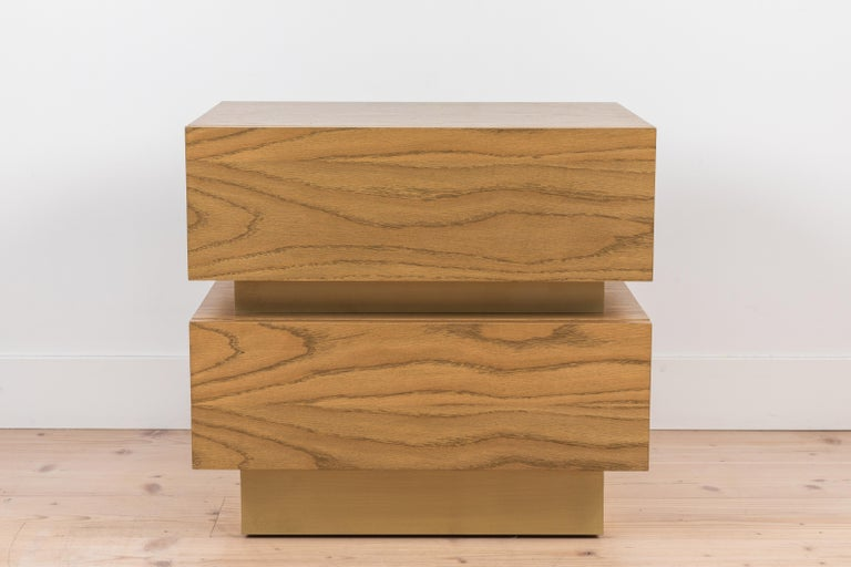 The stacked box nightstand is a bedside table with two drawers that is available in either American walnut, or white oak. Available in two sizes. Shown here in smoked oak with satin brass inset. 
