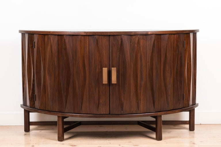The Griffin console features a demilune shaped case with parquet doors, brass hardware and a sculptural wood base. Available in American walnut or white oak. Shown here in light walnut.