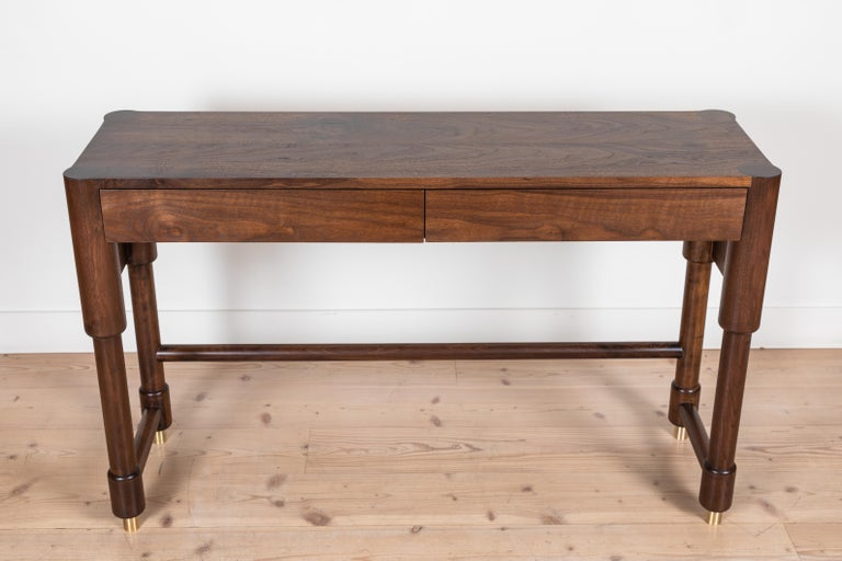 The Niguel Console features brass cap feet, a brass cross stretcher and lacquered interior drawers. Shown here in Light Walnut.   Available to order in various finishes with a 10-12 week lead time.