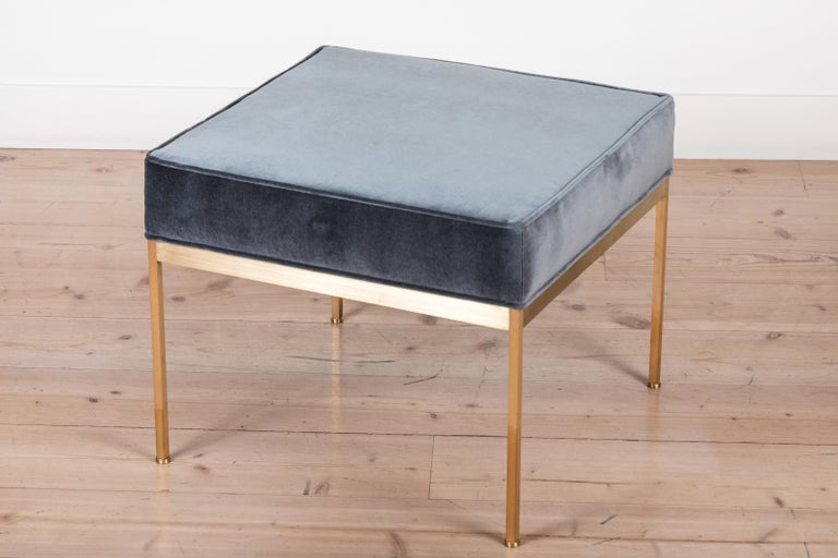 The square brass ottoman features a solid unlacquered brass base and an upholstered seat with piping. Each leg features a rounded leveler. 