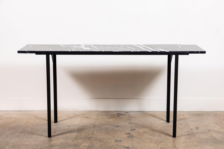 The Montrose console table features a powder coated steel base with a minimal honed travertine stone top. For indoor or outdoor use. Shown here in Negra Marquina Marble and Matte black. 