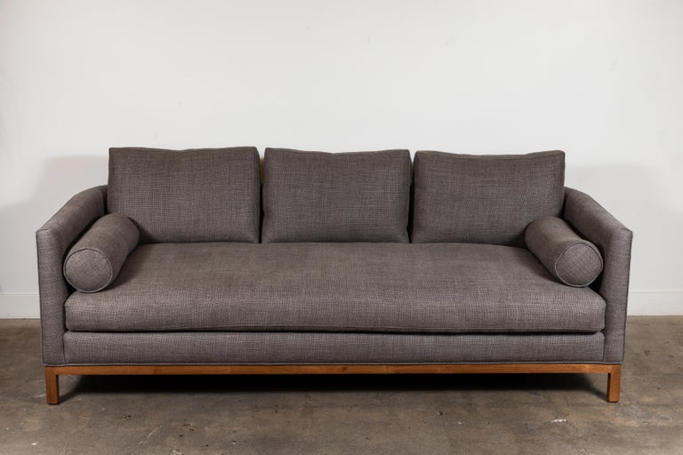 The curved back sofa is a tuxedo style sofa with curved corners and features a single down-wrapped, seat cushion with 3 down-wrapped, removable back cushions and two bolsters. The base can be made in American walnut, white oak or metal. Shown here
