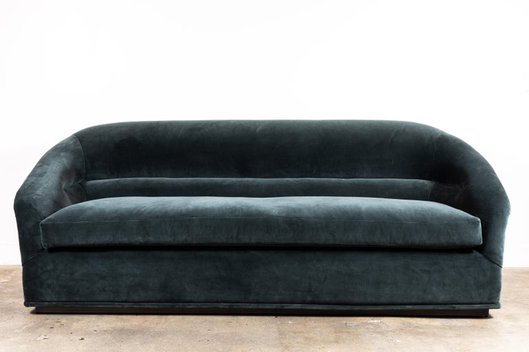 The Huxley sofa is inspired by 1970s lounge furniture. A curvaceous form with a single line tuft and long seat cushion rest atop a polished brass base.   Available to order in customer's own material with a 6-8 week lead time.   As shown: